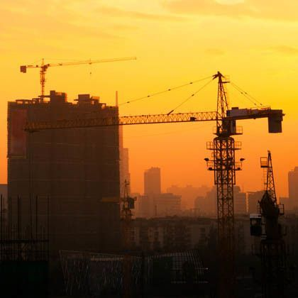 Silhouette of crane and buildings against orange sunset